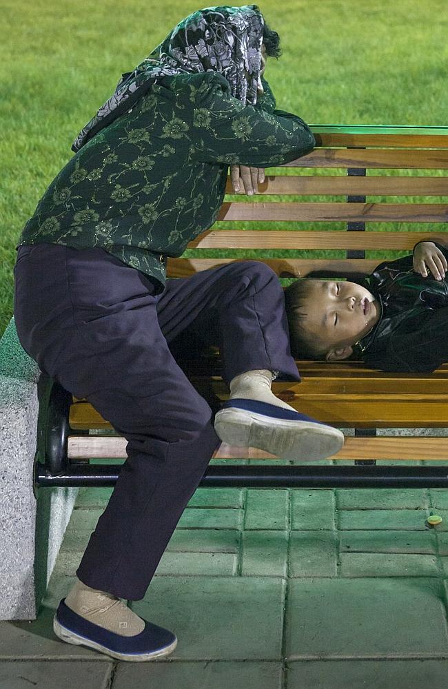 Mutter mit Kind ruhen sich auf einer Bank aus