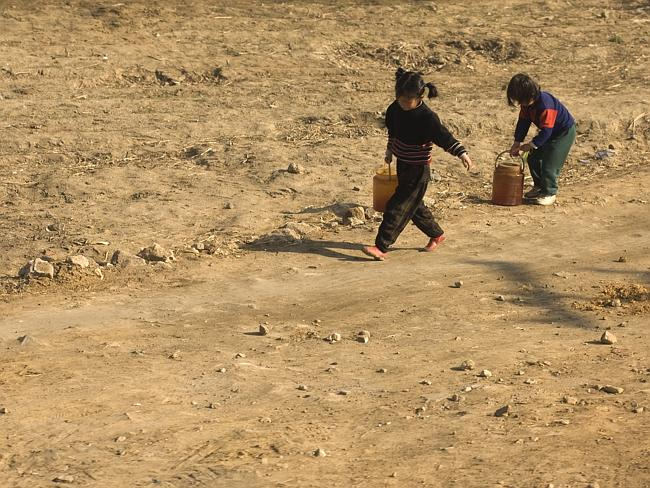 Arme Kinder tragen Wasser