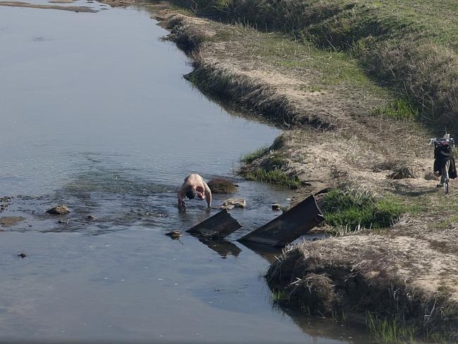 EIn Mann wäscht sich im Fluss