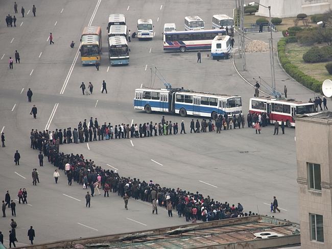 Menschen stehen in einer Schlange für den Bus